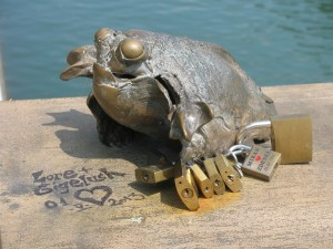 This toad-like creature on the bridge is clutching (?being clutched by) padlocks too