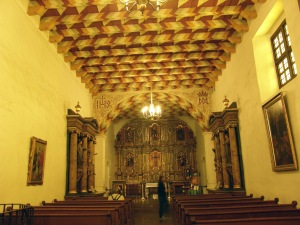 Inside the old Mission Chapel. Note the ceiling , side altars and main altar